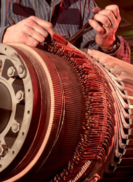 Machinist repairing brushes on large motor. Motor system management offers efficiency.
